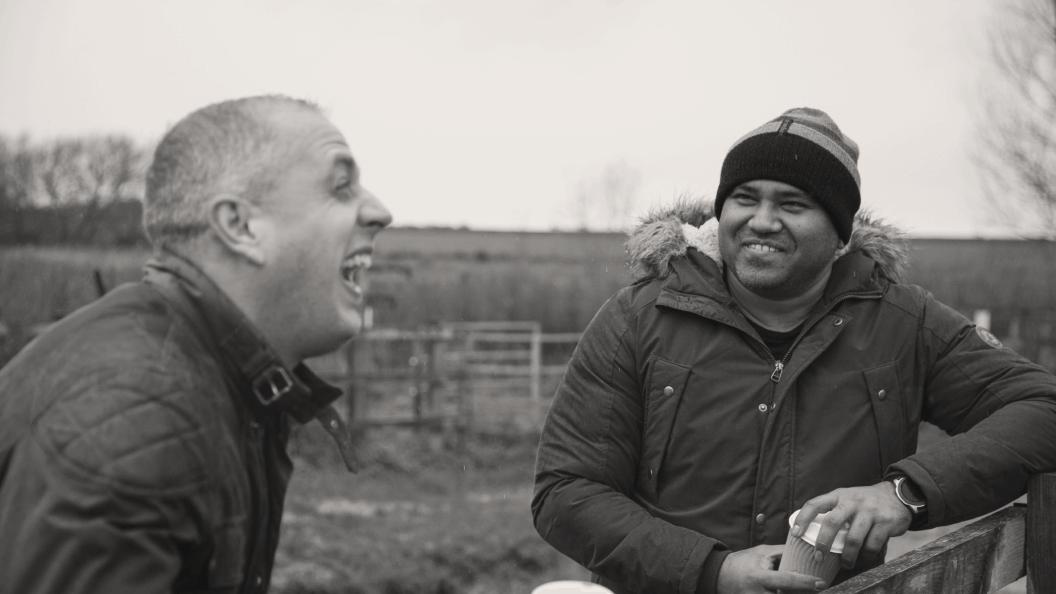 Two friends sharing a joke outside.