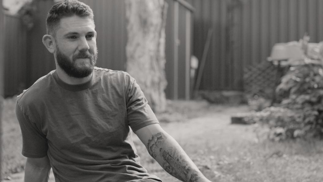 Portrait of man sitting in his backyard.