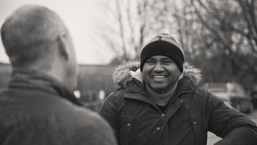 Smiling man having a conversation with a friend outside.