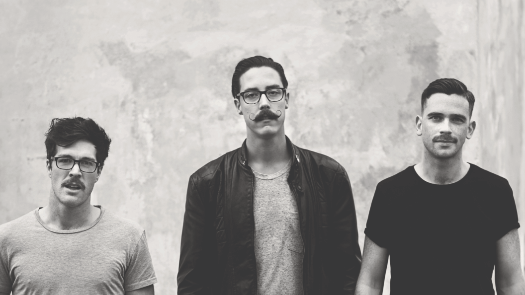 Portrait of three men with moustaches against concrete wall.