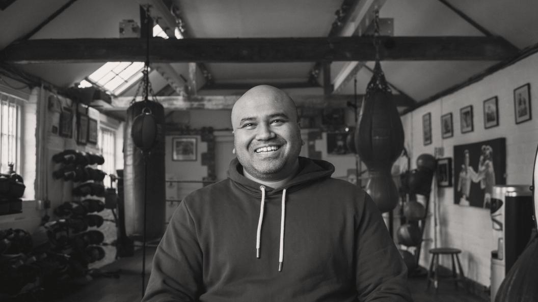 Portrait of man wearing hoodie in boxing gym.