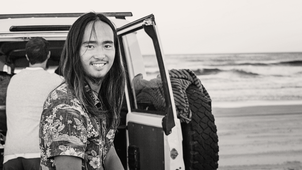 Portrait of man smiling with long hair at the beach, in front of four wheel drive.